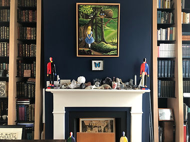 Image of a fireplace at the Peter Bullough Foundation with a painting depicting Alice in Wonderland