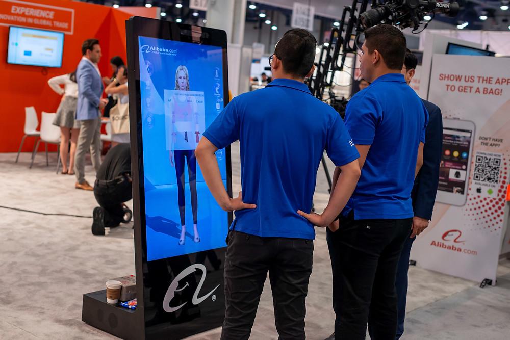 現場參觀者在體驗阿裡巴巴國際站的智能試衣鏡