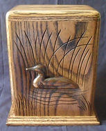 Carved Loon funeral urn shown in oak wood