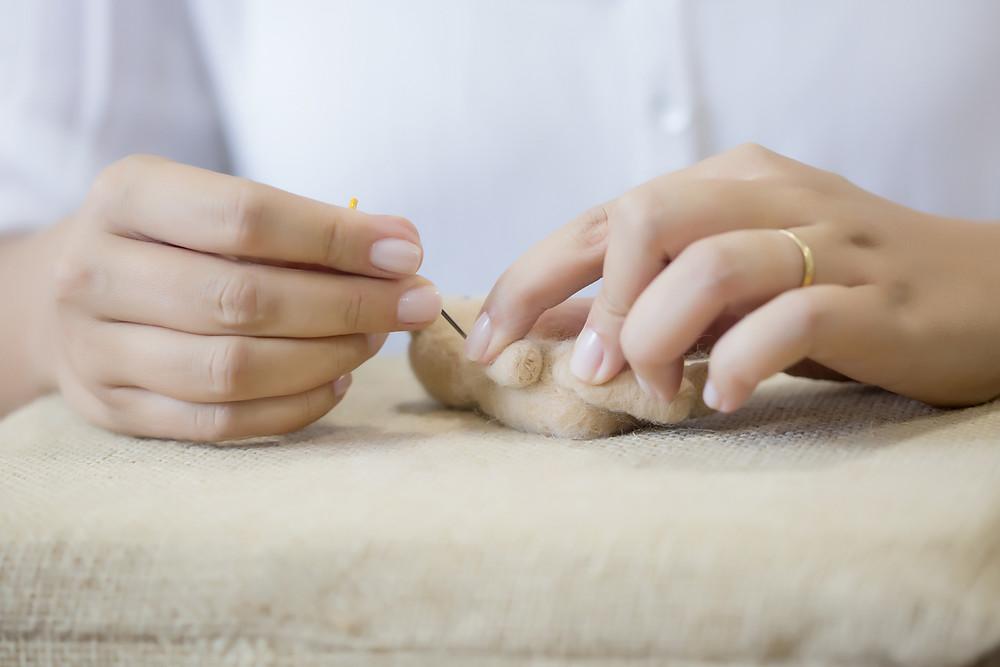 Foto de duas mãos feltrando um peça com agulha.