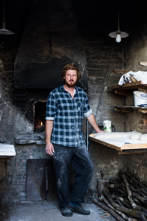 Milo Burr, one of the Cooks at  Spannocchia, stands at the outdoor brick  oven ready to make bread and pizza