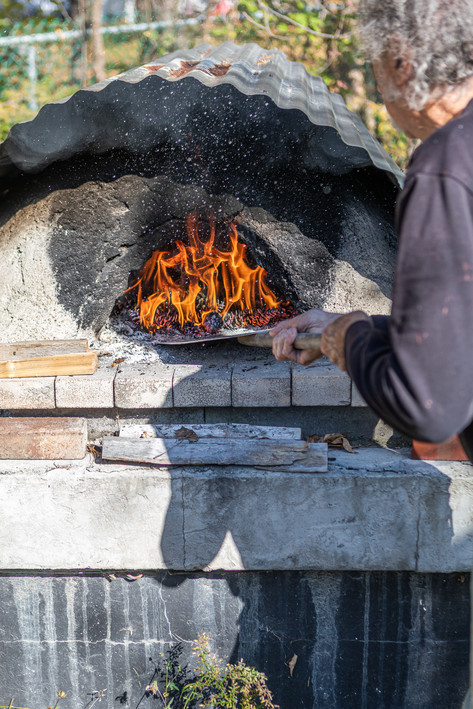 Silverstein uses a peel to adjust the flame in his outdoor, wood-fired oven.