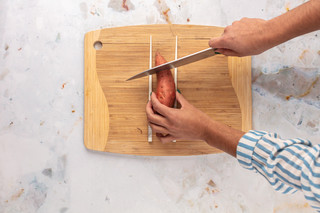 Using chopsticks as a guide helps to prevent slicing Hasselback potatoes all the way through.