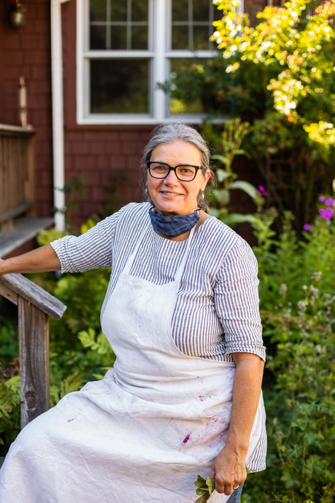 Celebrated food stylist Catrine Kelty on the stoop of her old Maine farmhouse.