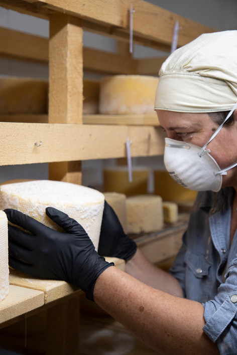 Allison Lakin rotates wheels of cheese as they are inside the cave at East Forty Farm in Waldoboro.