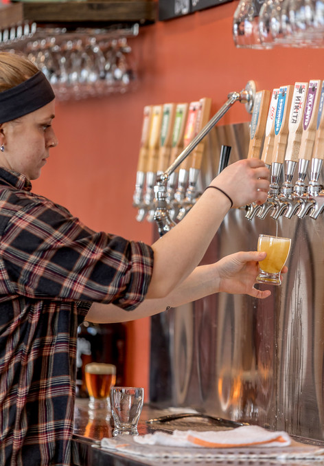 A bartender at Rising Tide Brewing Company  pours a flight of beers for a patron to taste
