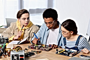 multicultural teenagers soldering comput