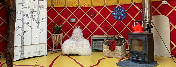 Interior of Cai Yurt with vibrant red walls, sheepskin rocker chair and Clearview wood burner stove
