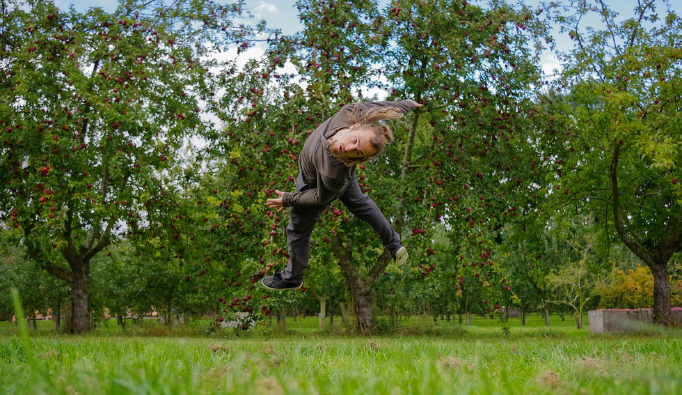 Hugh Stanier jumping in front of the apple trees at Dragon Orchard