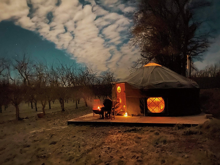 People enjoying a firepit next to Cai Yurt at nightime under a starry sky at Dragon Orchard