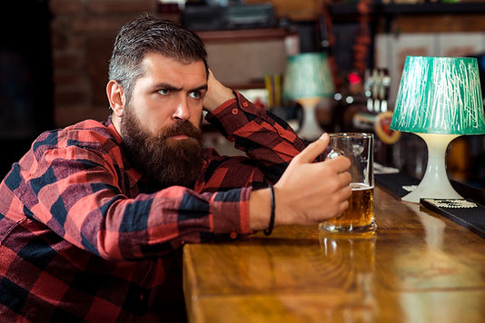 sad-man-drinking-beer-pub-single-bearded