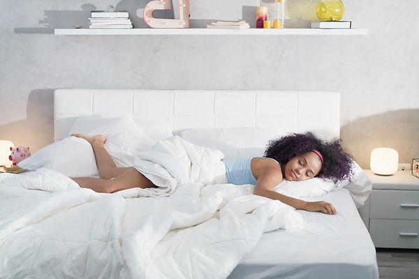 black-woman-sleeping-alone-in-large-bed-