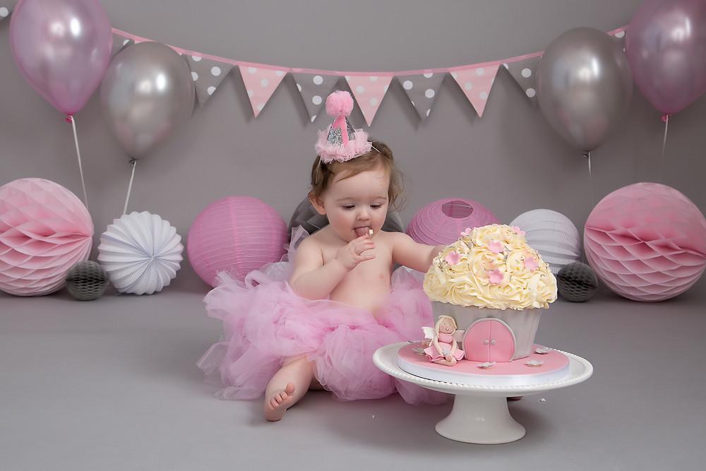 Minnie tasting her birthday cake at her cake smash