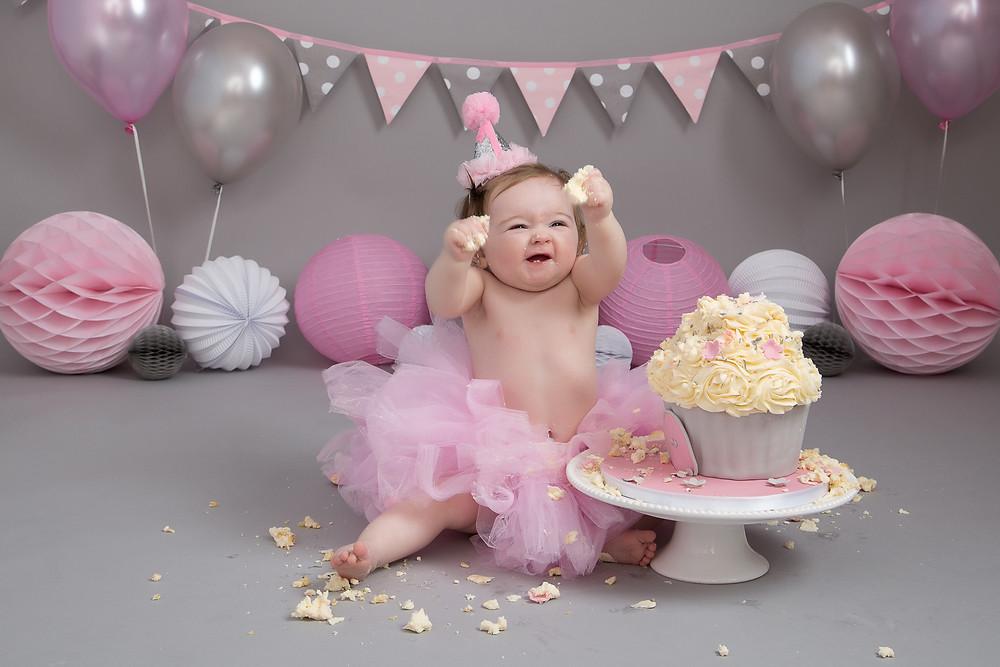 Squishing cake at a Petite Portraits Photography Cake Smash photoshoot