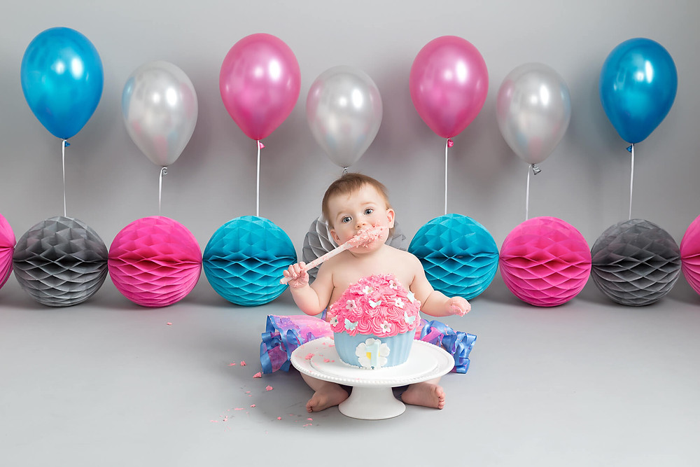 Eating with a spoon at her cake smash photo shoot sheffield rotherham Petite Portraits