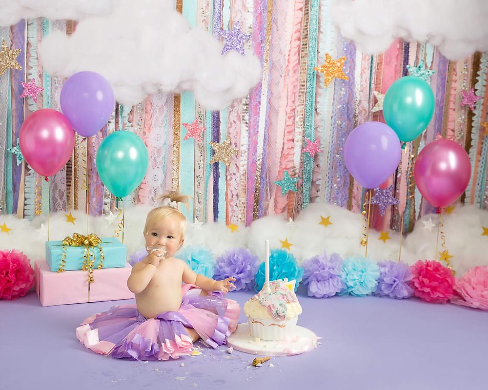 petite portraits photography cake smash baby tasting unicorn cake