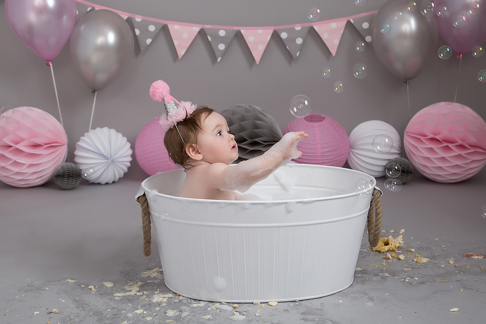 catching bubbles at a cake smash and splash photoshoot