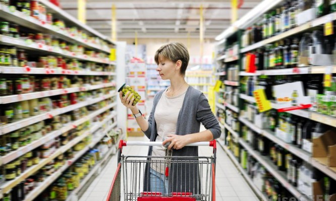 woman-with-cart-looking-at-canned-food-in-store-666x399