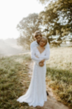 groom hugging bride from behind in a field at sunrise