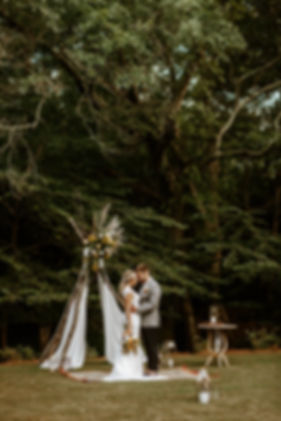 bride and groom face each other in front of teepee