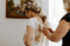hands buttoning up back of white wedding dress