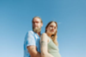 couple looks at camera with blue sky