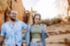 couple walks on red rocks and look at camera