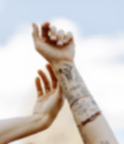 close up of girls arms with tattoos and jewelry