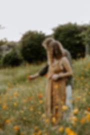 engaged couple picking wildflowers