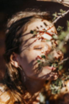 girl smiles in a bush with shadows on her face