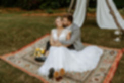 groom kisses bride sitting in his lap on a blue and red rug