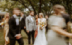 bride and groom smile at each other while bridal party runs