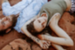couple lays down on red rocks in colorado