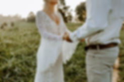 bride and groom holding hands in a field