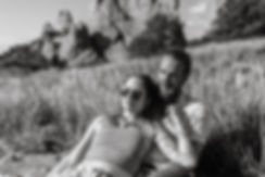girl in sunglasses sitting in guys lap in black and white