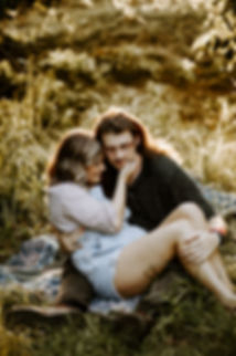 girl sitting in long haired guys lap an holding his face