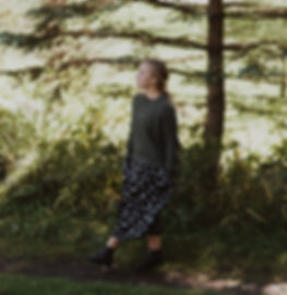 blonde girl walking in the woods in a dress
