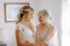 bride and grandmother smiling at each other