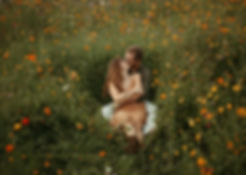 engaged couple kissing in a wildflower field
