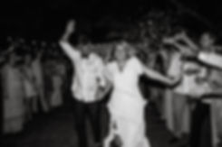 bride and groom running and laughing in black and white