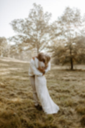 groom and bride embrace in a field at sunrise