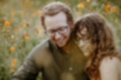 girl resting head on boy's shoulder in a wildflower field
