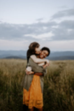 guy hugs girl from behind with mountains in the background