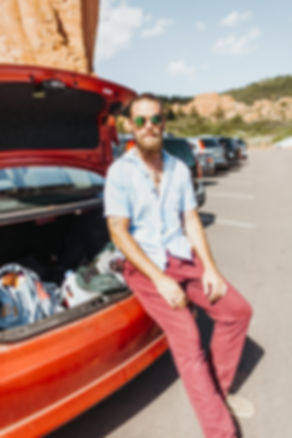 guy in sunglasses sitting on a car in a parking lot