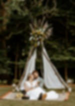 bride and groom sit on a blue and red rug in front of a teepee