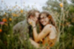 boy kissing girl on the cheek in wildflower field