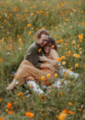 couple cuddling in a flower field at furman university