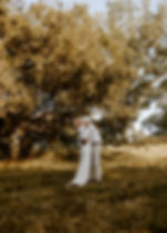 bride and groom hug in a field on the grounds of biltmore estate