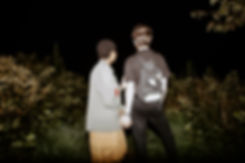couple holds hands at night with flash