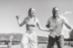 couple holds hands and runs together in black and white